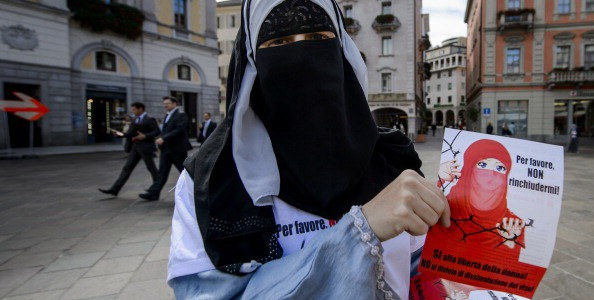 """Islamic Central Council of Switzerland (ICCS - CCIS) member Nora Illi, one of the few Swiss women wearing the niqab, poses on September 18, 2013 while distributing flyers reading """"Please don't lock me up"""" in Lugano against an upcoming cantonal vote on banning face-covering headgear in public places. Ticino will become on September 22 the first Swiss canton to hold a so-called """"anti-burqa"""" referendum. Although the initiative does not explicitly target Muslims--the phrasing to be voted on is """"nobody in public streets or squares may veil or hide their face""""--it is directed against the burqas and niqabs. Political commentators say the initiative has good chances of being accepted.  AFP PHOTO / FABRICE COFFRINI        (Photo credit should read FABRICE COFFRINI/AFP/Getty Images)"""